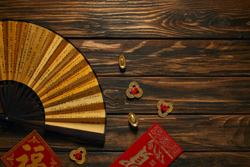 top view of fan with hieroglyphs and golden chinese decorations on wooden table