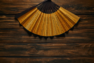 top view of decorative black and golden fan with hieroglyphs on wooden surface