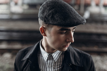 stylish gangster man posing on background of railway. england in 1920s theme. fashionable brutal confident. atmospheric moments. space for text