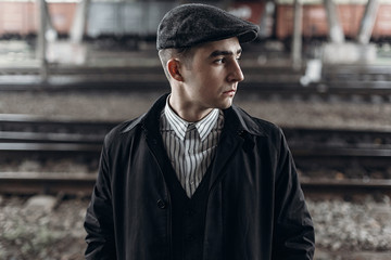 stylish man in retro outfit posing on background of railway. england in 1920s theme. fashionable look of brutal confident man. atmospheric moments.
