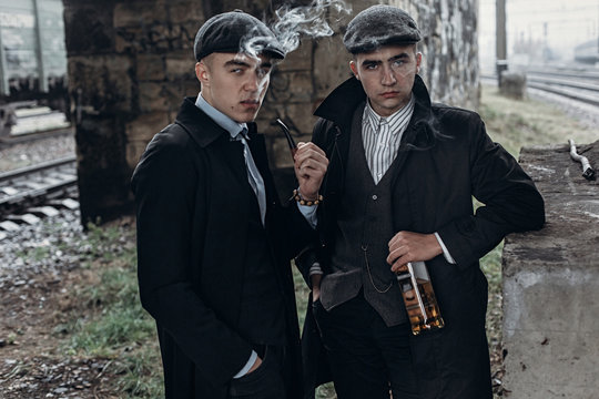 stylish gangsters men, smoking. posing on background of railway with bottle of alcohol.sherlock holmes and doctor watson. england in 1920s theme.