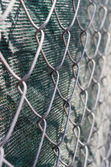 Close up of chain link fence with green fabric