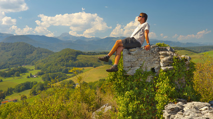 Tourist sitting on the ruins of the former castel of Montousse with Pyrenees on background, France
