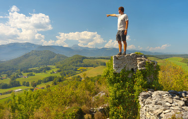Tourist standing on the ruins of the former castel of Montousse showing towards Pyrenees on background, France