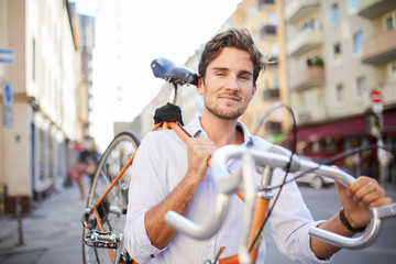 Portrait of content young man carrying his racing cycle on shoulder in the city