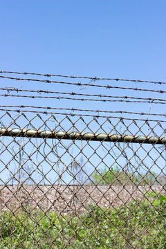 Chain link fence with barbed wire blue sky