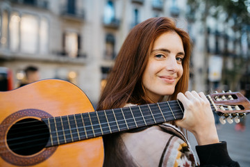 Portrait of smiling redhead young woman holding guitar outdoors Fototapete