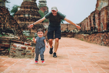 Thailand, Ayutthaya, Father and daughter running in the ancient ruins of a temple at Wat Mahathat