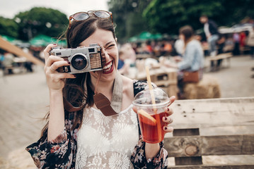 happy hipster woman in sunglasses having fun with photo camera and drinking lemonade. stylish boho girl holding cocktail and smiling at street food festival. summertime
