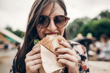 stylish hipster woman eating juicy burger. boho girl biting yummy cheeseburger, smiling at street food festival. summertime. summer vacation travel picnic. space for text Wall mural