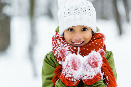 cute african american child showing white snow an smiling at camera in winter forest