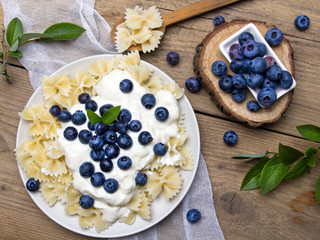 Tasty pasta with fresh organic blueberries and vanilla cream. Sweet dinner on retro wooden table.