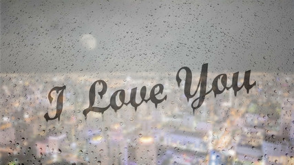Draw letters I love you by hand on a glass with water drops droplets with night cityscape background.