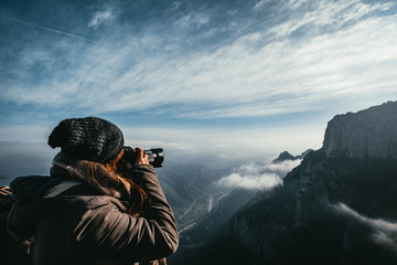 Woman Photographer takes photo of Mountain Winter Landscape with clouds.