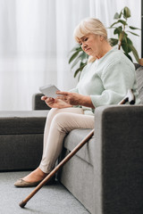 sad retired woman with blonde hair looking at photos while sitting on sofa