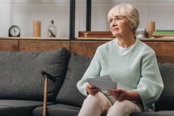 upset retired woman with blonde hair holding old photos while sitting on sofa