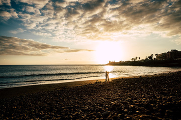 couple in love kiss with amazing colored golden sunset in the background. beach and ocean wave scenic place in Tenerife. romantic and tenderness concept for man and woman in vacation