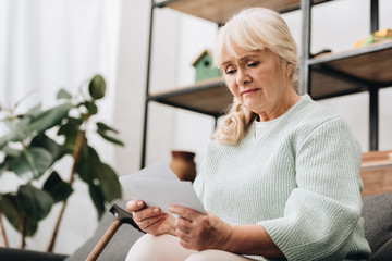 sad retired woman holding photos in living room