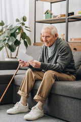 sad pensioner with grey hair looking at photos while sitting on sofa