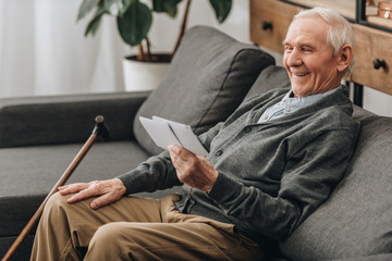 happy pensioner with grey hair looking at photos and sitting on sofa