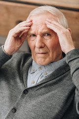 senior man with grey hair having headache
