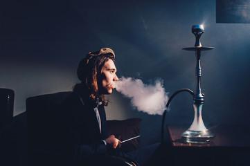 Retro portrait of a young man smoking hookah