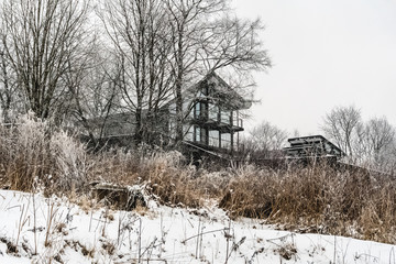 Modern house covered with snow among the trees. In the winter.