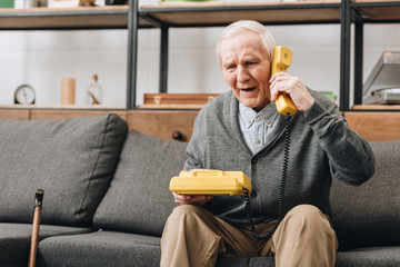 retired man talking on retro phone while sitting on sofa