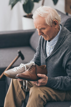 senior man choosing between classic and modern shoes