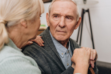 selective focus of sad pensioner looking at retired wife at home