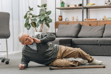 old men falled down on floor and touching neck