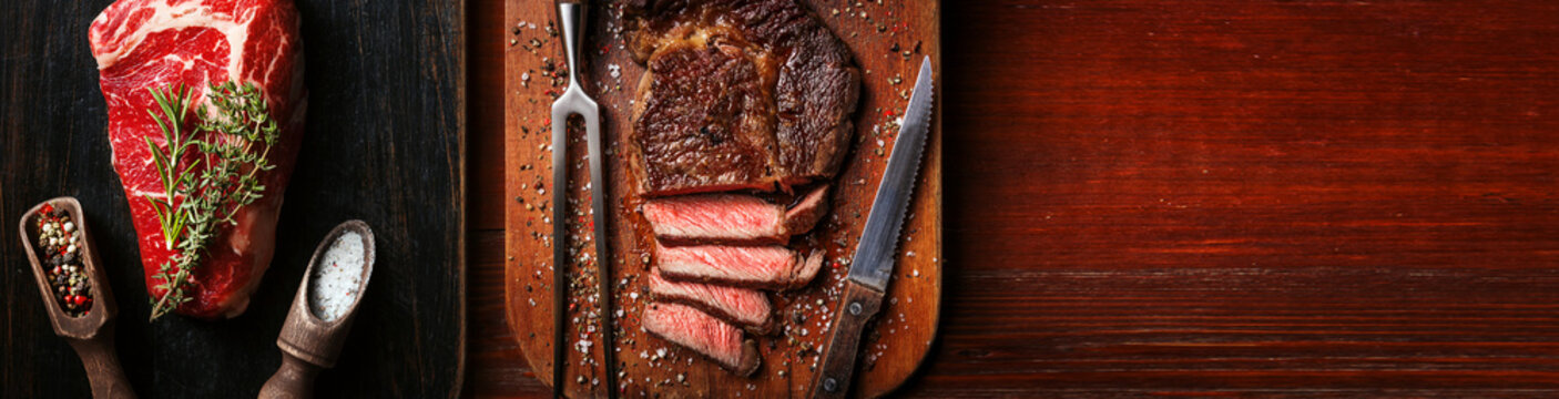 a piece of fresh marbled beef on a wooden background, with spices for cooking steak