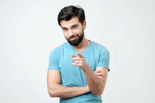 Portrait of happy hispanic man with beard pointing at you.
