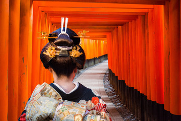 Foto op Plexiglas Asia land Woman in traditional kimono walking at torii gates, Japan