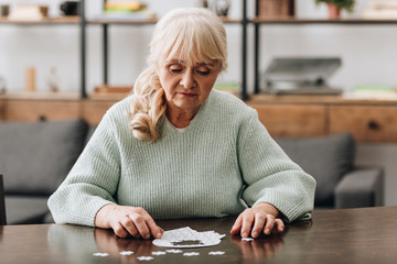 Wall Mural - senior woman looking at puzzle pieces on table