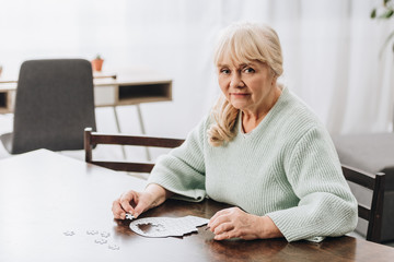 Wall Mural - blonde retired woman playing with puzzles at home