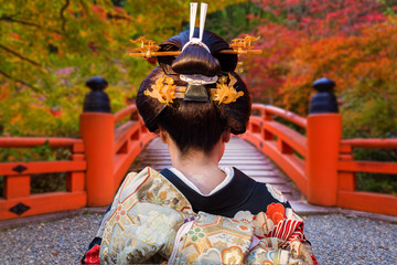 Foto op Plexiglas Asia land Woman in traditional kimono walking at the colorful maple trees in autumn, Japan
