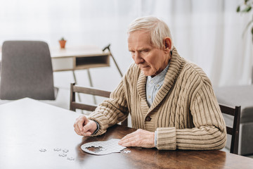 pensioner with grey hair playing with puzzles at home Wall mural