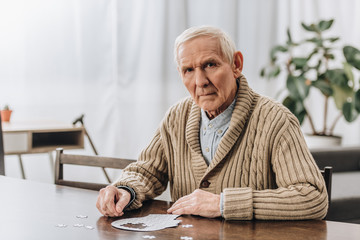sad pensioner with grey hair playing with puzzles at home
