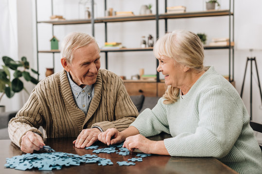 happy senior couple playing with puzzles at home