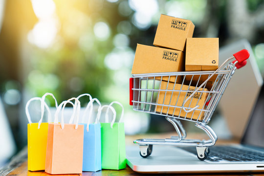 Shopping online concept with cart, bags, package boxes and laptop on table with copy space