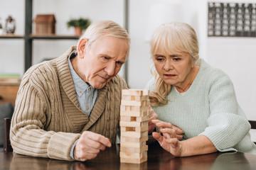 Wall Mural - retired couple playing jenga game on table