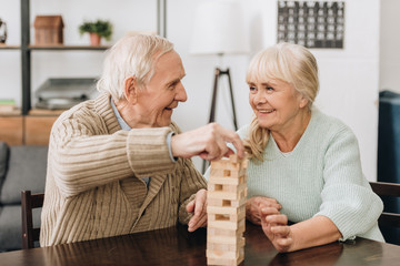 Wall Mural - smiling pensioners playing jenga game on table