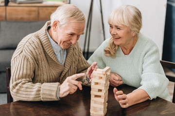 Wall Mural - cheerful retired husband and wife playing jenga game on table