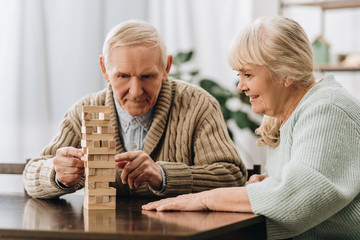 Wall Mural - retired husband and wife playing jenga game on table
