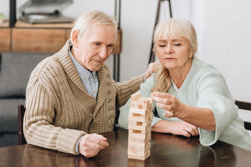Wall Mural - retired couple playing jenga game on table at home