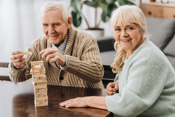 Wall Mural - happy pensioners playing jenga game on table
