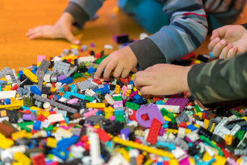 Close up of colorful plastic bricks on the floor. Early learning. Developing toys. Children's plastic constructor on the floor. Children's hands play a little constructor