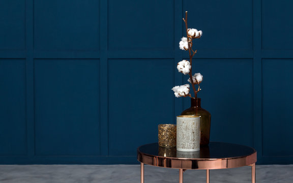 Modern Vases on metal copper side table in room with blue walls