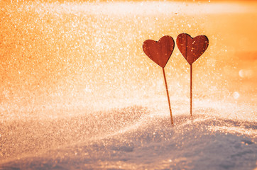 Two wooden hearts in orange sunset light